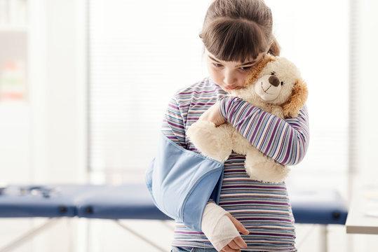 Cute girl with arm brace and teddy bear