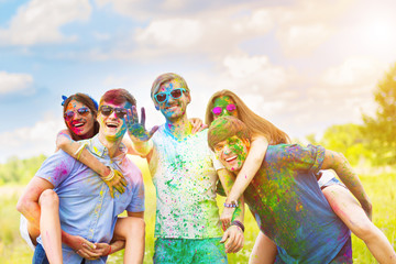 Cheerful and happy friends soiled by bright colorful paints smiling and laugh on spring summer festival on nature. Company of young people having fun with holi paints. Holi party concept. Wall mural