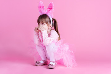 Cute pink young girl child daughter wears pink dress like rabbit playing in easter holiday game with rabbit ears on isolated pink background. Spring is coming and Easter holiday concept