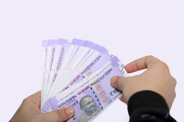 Man hand is holding Indian 100 rupee currency. Isolated on the white background.