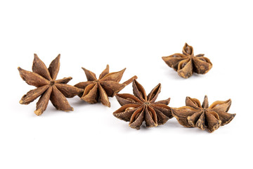 Group of five whole dry brown star anise fruit isolated on white background