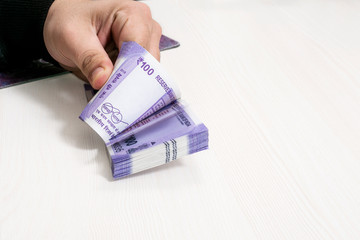 Portrait of hand with new Indian currency notes. Isolated on the white background.
