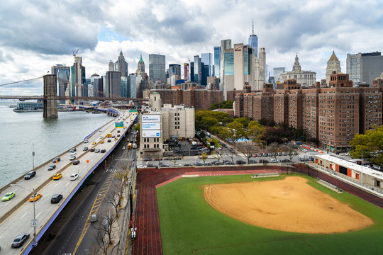 A baseball field along the FDR and East River with views towards the Brooklyn Bridge and Lower Manhattan, New York
