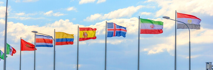 National flags of the countries participating in the finals of the FIFA World Cup against a blue cloudy sky.