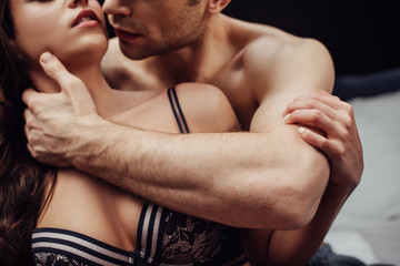 cropped view of man passionately touching neck of sexy woman isolated on black