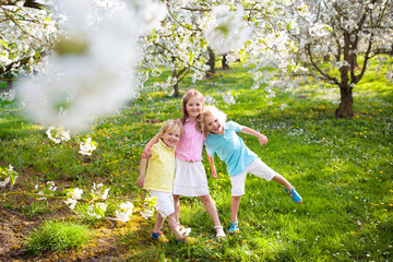 Kids in spring park. Child at blooming cherry tree