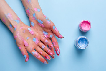 Women's hands with watercolor brushstrokes on blue background