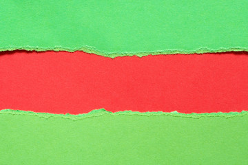 Torn green paper with a red background Wall mural