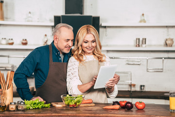 happy woman using digital tablet while standing with husband in kitchen near vegetables