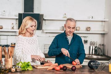 attractive woman cutting carrot near husband holding knife near tomato in kitchen