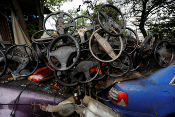 Steering wheels are seen at a car junkyard on the outskirts of Jakarta