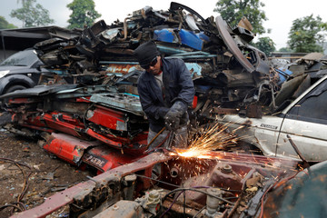 A worker uses blow torch to break parts of an old car for scrap metal at a car junkyard on the outskirts of Jakarta