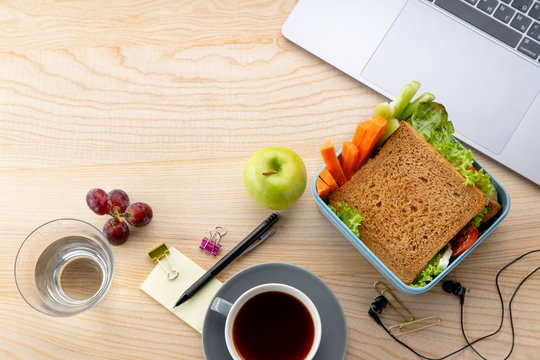 Overhead image of healthy sandwich in plastic container with some fruits on wooden table next to opened laptop. Daily office or school lunch concept