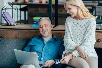 cheerful man looking at laptop near wife holding credit card