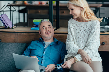 cheerful man using laptop near attractive wife holding credit card