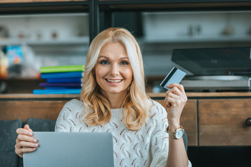 happy woman holding credit card while using laptop at home