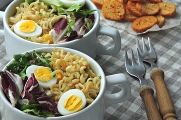 Noodle soup with quail eggs and mix salad