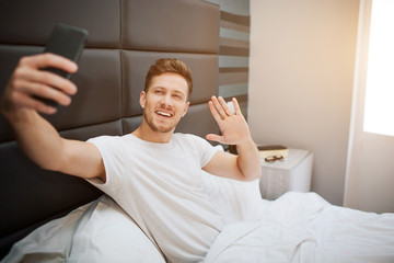 Young cheerful man in bed this morning. He and pose on phone camera. Guy wave with hand and smile. Daylight.