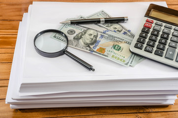 a bunch of white paper on a wooden table, a calculator, a pen, magnifier and dollars