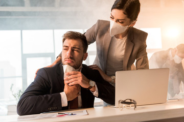 selective focus of  businesswoman in mask standing near scared colleague in office with smoke