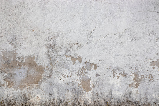 Gray wall ruined by time, bad weather and humidity. Cracks, mold, peeling paint and plaster. Texture, material background.