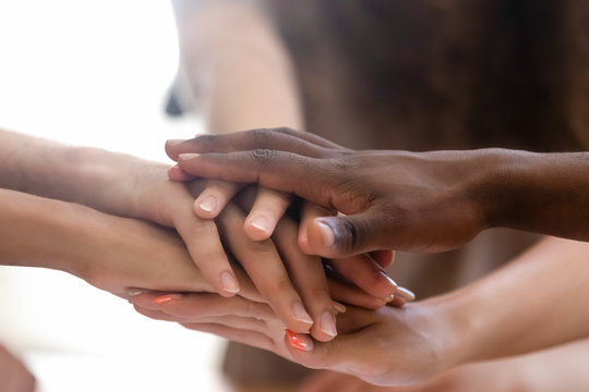 Diverse people group stacked joined hands in pile closeup view