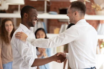 Caucasian executive handshaking promoting successful happy african worker expressing gratitude