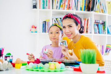 Happy mother paints eggs with her daughter