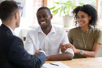 Happy black couple handshaking realtor insurer landlord at meeting
