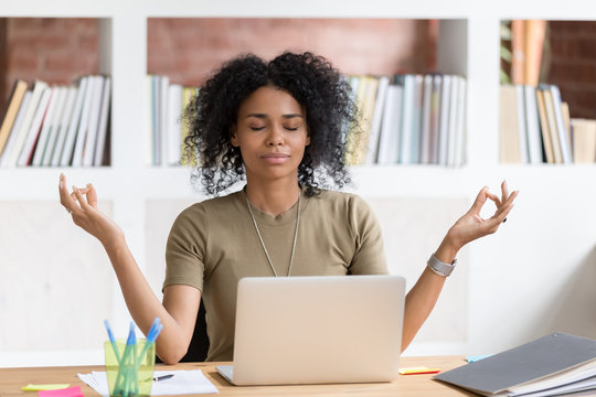 Calm black businesswoman taking break meditating doing yoga at work