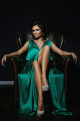 Woman wearing beautiful green silk dress is posing on leather couch