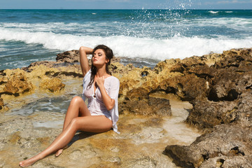 Sexy woman in wet tunic is posing on the beach with rocks