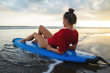 Woman sitting on surfboard on the beach after her surfing session