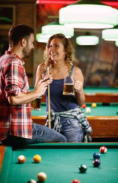 smiling woman flirting with man during billiard game.