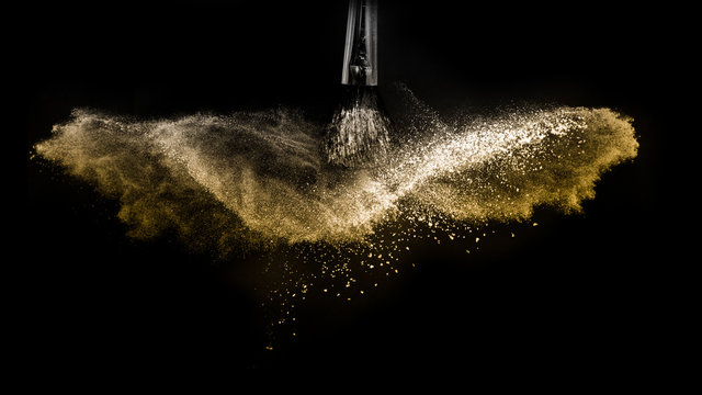 Cosmetic brush with golden cosmetic powder spreading for makeup artist and graphic design in black background, look like a luxury mood.