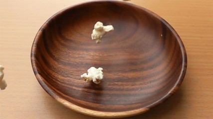 Fototapete - Popcorn fall into a wooden plate on a table in Slow Motion