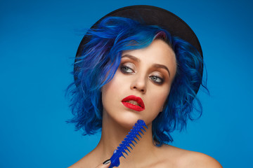 Portrait of a woman with blue hair in a black hat and with a blue hairbrush in her hand