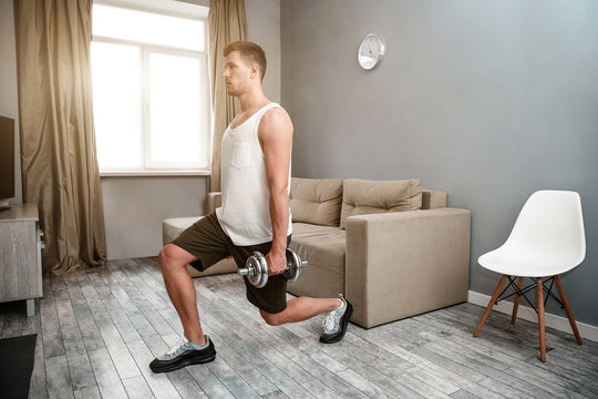 Young well-built man go in for sports in apartment. He does forward lunges with dumbbells. Concentrated young man have workout. Right leg goes first.