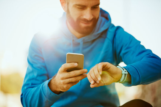 Close up of young bearded man looking at smart watch and holding smart phone in other hand.