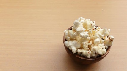 Fototapete - Drop wooden bowl filled with popcorn on the top of wooden table in Slow Motion