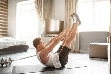 Young well-built man go in for sports in apartment. He lying on back and reach feet with hands. Young man stretching. Yoga exercise.