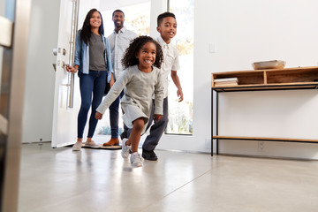 Parents And Children Returning Home Opening Front Door And Running Inside