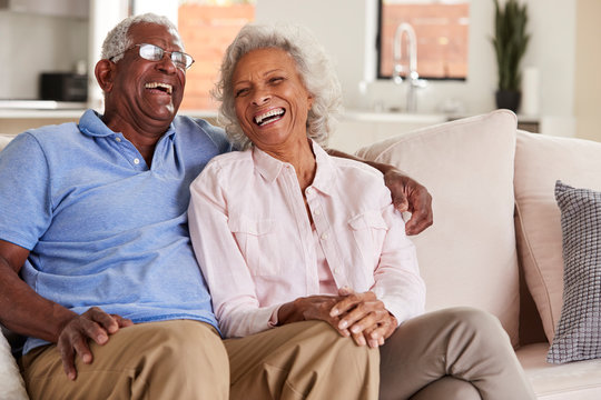 Loving Senior Couple Sitting On Sofa At Home And Laughing Together