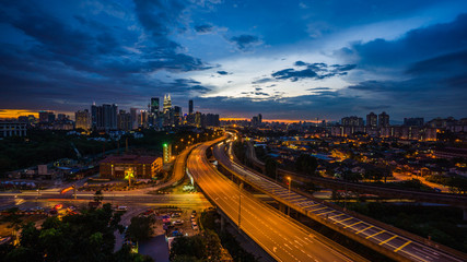 Wall Murals Kuala Lumpur Kuala Lumpur city skyline during dramatic sunset with elevated highway leading into the city.
