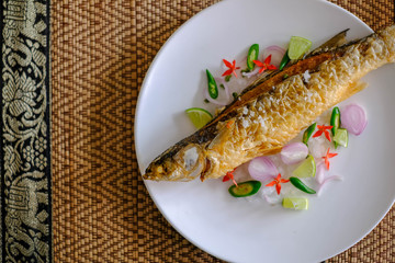 deep fried fish season with salt and herb on mat