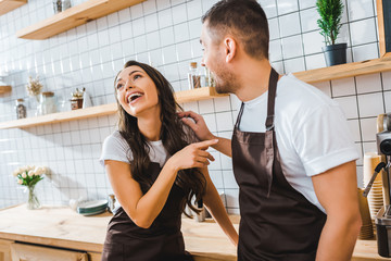 cashiers in aprons talking and laughing near bar counter in coffee house