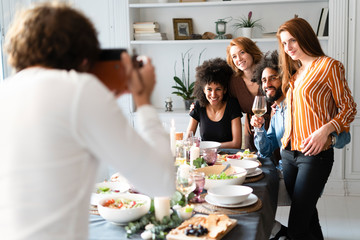 Friends taking a group picture as memory of a dinner party