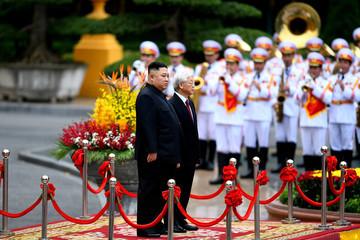 North Korea's leader Kim Jong Un and Vietnam's President Nguyen Phu Trong address a ceremonial guard of honor during a welcoming ceremony at the Presidential Palace in Hanoi