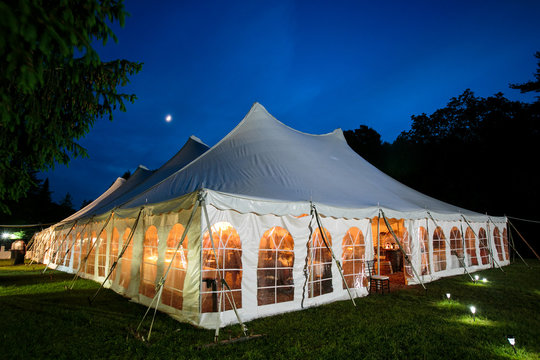 A wedding tent at night with blue sky and the moon. The walls are down and the tent is set up on a lawn - wedding tent series