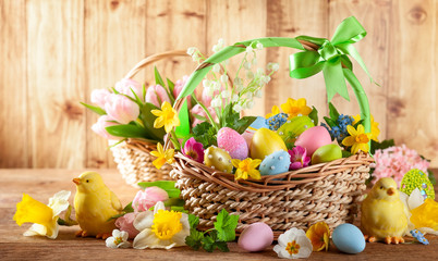 Easter composition spring flowers  and colorful Easter eggs in basket.